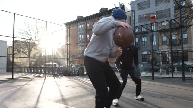 two friends candidly play one on one basketball at a local court in brooklyn, nyc - basketball stock-videos und b-roll-filmmaterial