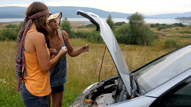 vídeos de stock, filmes e b-roll de dois amigos verificar o óleo no motor do carro - óleo de motor