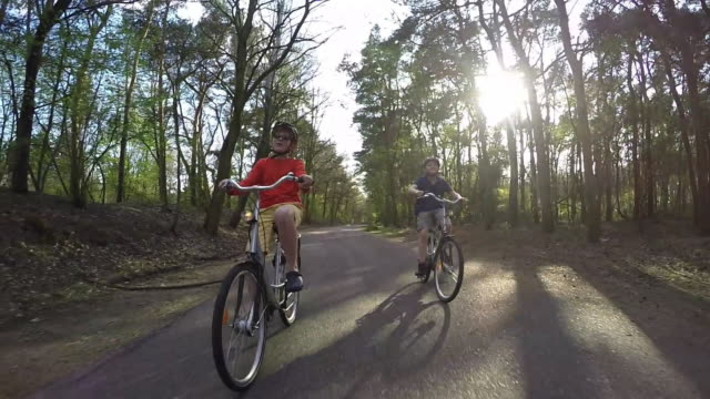 Two friends cycling together.Wide angle slow motion.