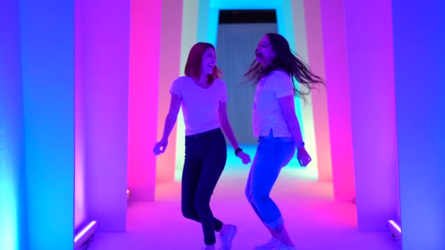 two friends dancing and having fun at colorful tunnel - hipster person stock videos & royalty-free footage