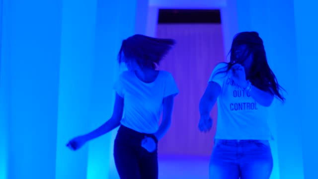 vídeos de stock, filmes e b-roll de dois amigos dançando e se divertindo no túnel colorido - espaço para texto