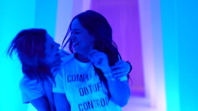 vídeos de stock, filmes e b-roll de dois amigos dançando e se divertindo no túnel colorido - multi coloured