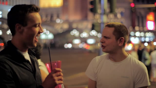 vidéos et rushes de two friends drink together on the strip in las vegas. - amitié masculine