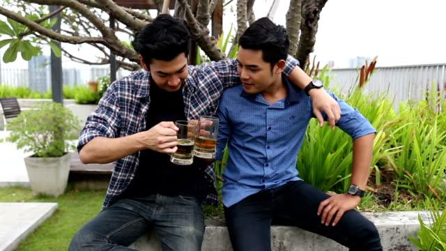 vidéos et rushes de deux amis buvant et riant sur le toit - en dernier