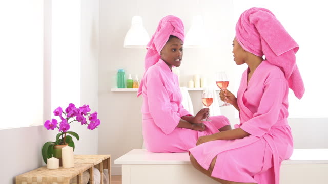 Two friends drinking wine in spa