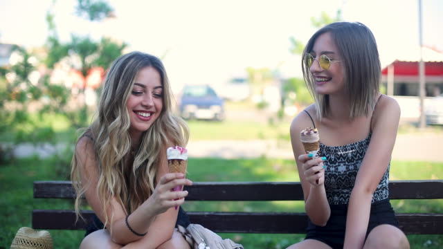 two friends eating ice cream on the bench - bench stock videos & royalty-free footage