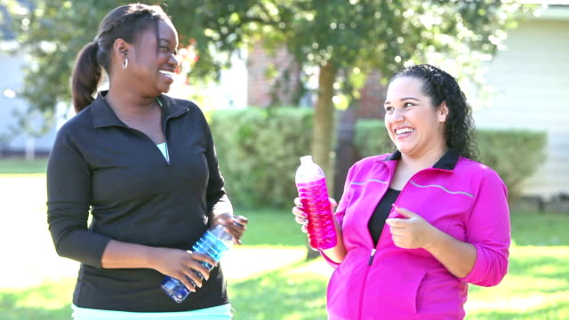 Two friends exercising together, stop to drink water