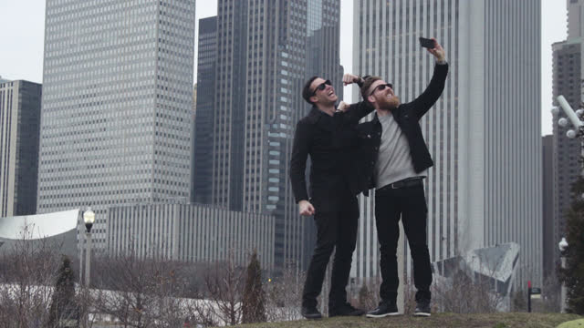 Two friends flex muscles and pose for smartphone selfies in Chicago park with city skyline in background.