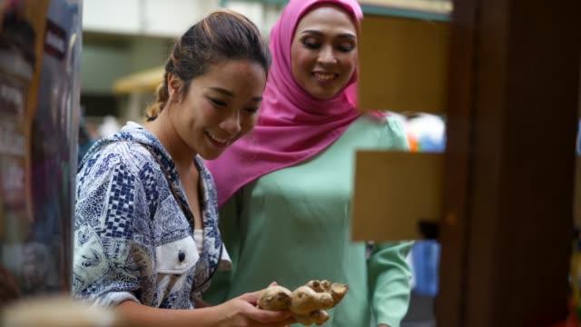 vidéos et rushes de deux amis ayant shopping au marché ensemble - foulard
