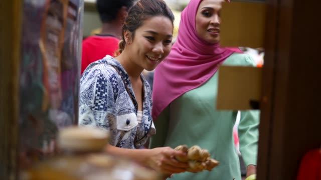två vänner som har shopping på marknaden tillsammans - krydda bildbanksvideor och videomaterial från bakom kulisserna