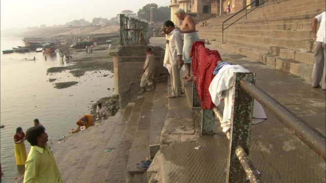 two friends help a gray-haired man wrapped in a dhoti walk down the steps of a ghat. - dhoti video stock e b–roll
