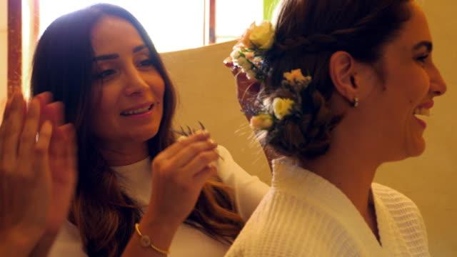 vídeos de stock, filmes e b-roll de ms two friends helping put flower in brides hair before wedding - preparação