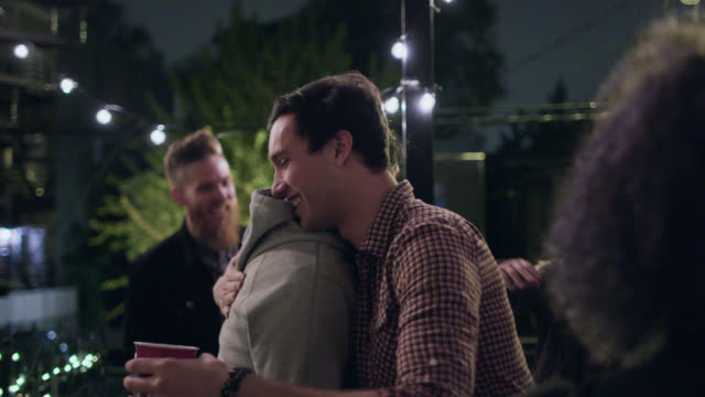 MS SLO MO. Two friends hug in greeting at rooftop party.