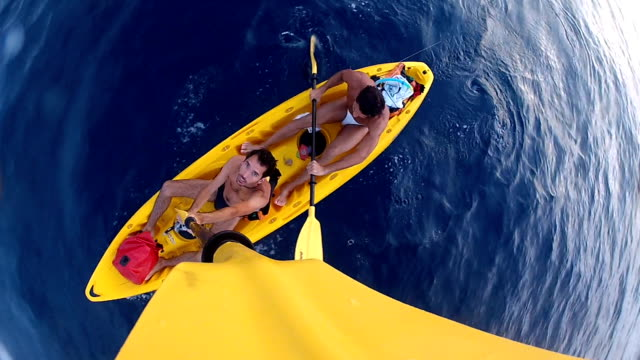 Two friends kayaking together in a yellow kayak in summertime