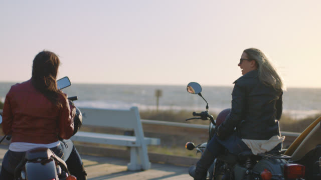 SLO MO. Two friends laugh together on motorcycles on windy day by the ocean.