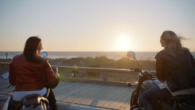 slo mo. two friends laugh together on motorcycles overlooking the ocean at sunrise. - horizont stock-videos und b-roll-filmmaterial