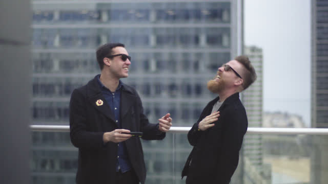 Two friends look at smartphone and laugh on balcony of Chicago high rise.