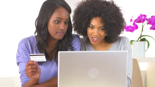 Two friends making online purchase with laptop