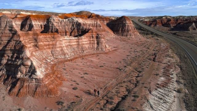 vídeos y material grabado en eventos de stock de dos amigos, hombre y mujer, turistas, paseando por la carretera en el cañón en utah, estados unidos - arcilla