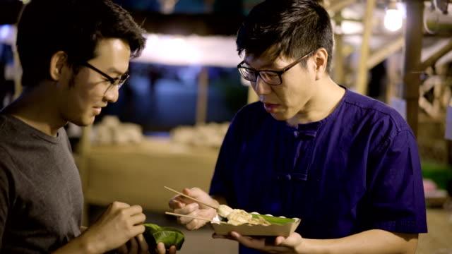 Zwei Freunde treffen auf lokalen Nachtmarkt für Lebensmittel