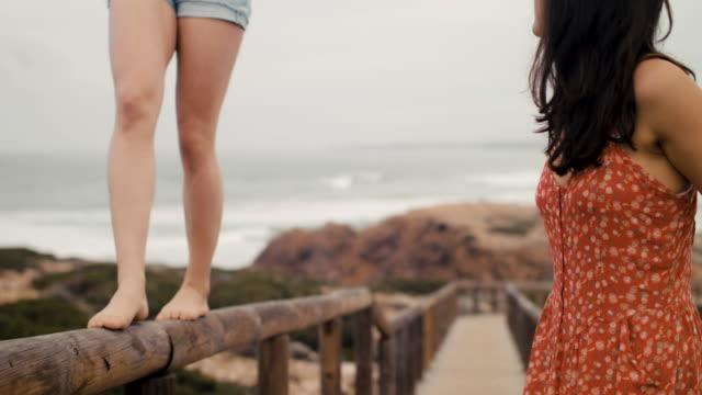 two friends on boardwalk, balancing on railing - boardwalk stock videos & royalty-free footage