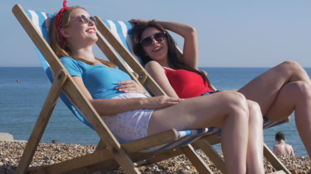 Two friends on deckchairs at the beach.