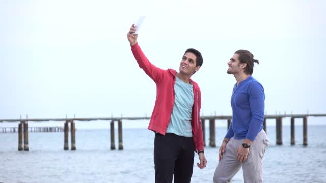 vídeos de stock, filmes e b-roll de dois amigos na praia em - homem homossexual