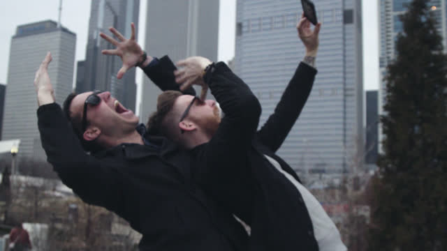 two friends pose for crazy smartphone selfie and laugh in chicago park overlooking city skyline. - generation y stock-videos und b-roll-filmmaterial