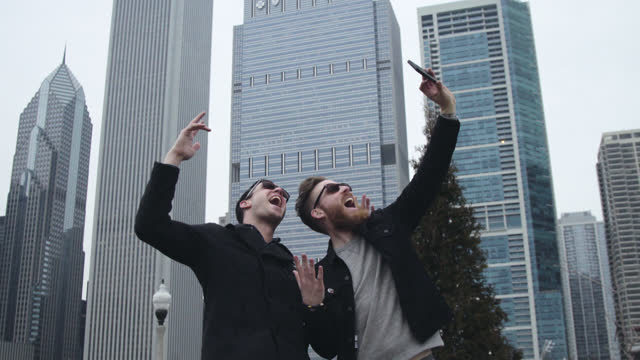 two friends pose for smartphone selfie in chicago park with city skyline in background. - selfie stock-videos und b-roll-filmmaterial