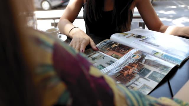 vídeos y material grabado en eventos de stock de dos amigos leyendo revista y hablando mientras están sentados en el café - female friendship
