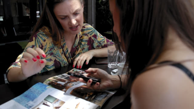 two friends reading magazine and talking while sitting in cafe - magazine publication stock videos & royalty-free footage