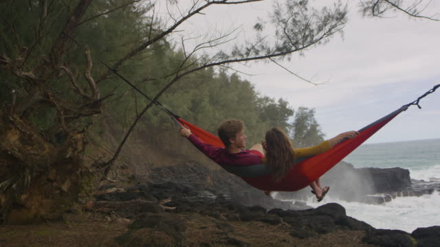 Two friends relaxing in hammock in secluded cove