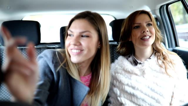vidéos et rushes de deux amis monte dans un taxi - siège arrière de passager
