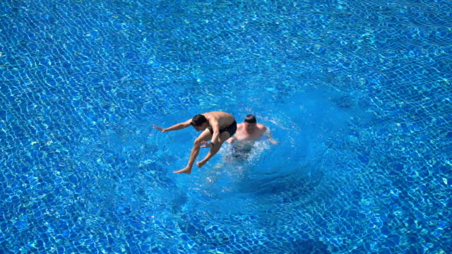 slo mo - two friends riding the neck and jump in swimming pool - swimming shorts stock videos & royalty-free footage