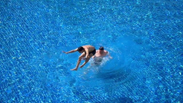 たいまつ - 2 つの友人の首とジャンプを乗馬スイミング プールで - 水泳パンツ点の映像素材/bロール