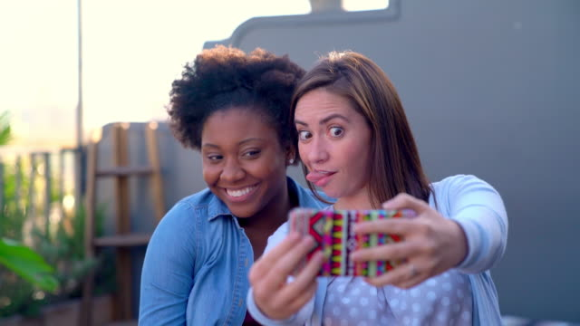 Two friends sat outside at early evening taking selfies