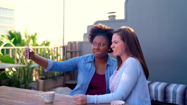 two friends sat taking selfies outside in the early evening sun - fotografia immagine video stock e b–roll