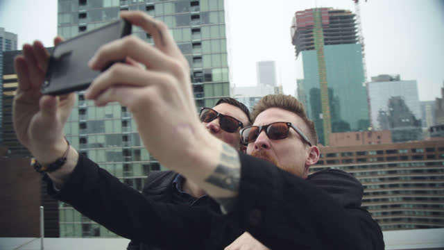 two friends take funny smartphone selfies overlooking chicago skyline. - facial hair stock videos & royalty-free footage