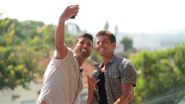 Two friends take smartphone selfie on Rio rooftop