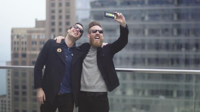vídeos de stock e filmes b-roll de two friends take smartphone selfie on roof of chicago high rise. - comunidade