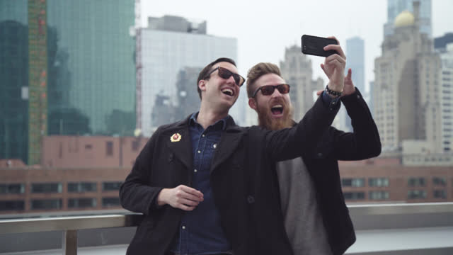 two friends take smartphone selfie with city skyline from chicago rooftop. - photography themes stock-videos und b-roll-filmmaterial