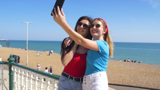 two friends taking a selfie at the beach. - brighton brighton and hove stock-videos und b-roll-filmmaterial