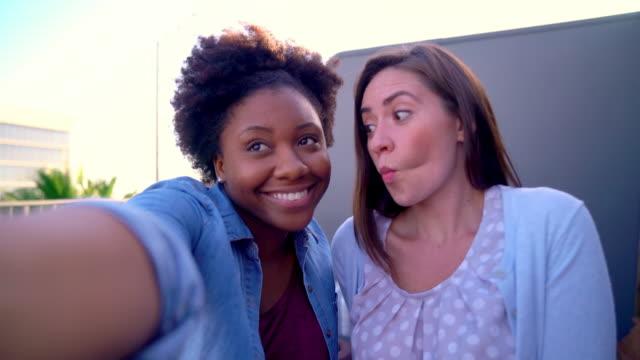 Two friends taking selfies outside