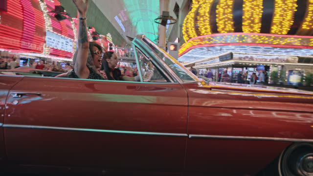 Two friends throw hands in the air driving through bustling downtown Las Vegas in classic red convertible.