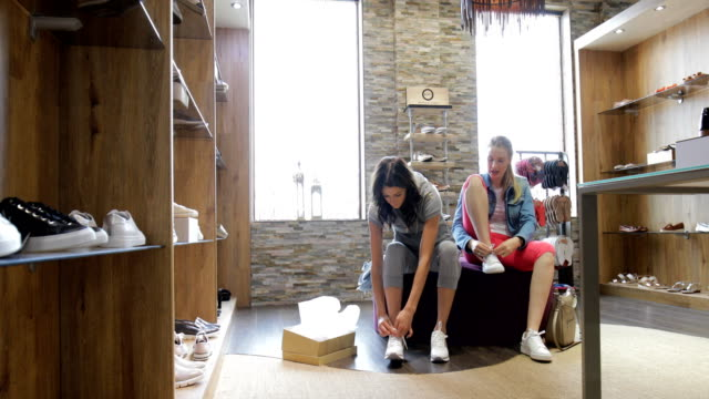 two friends trying on shoes - scarpe da ginnastica video stock e b–roll