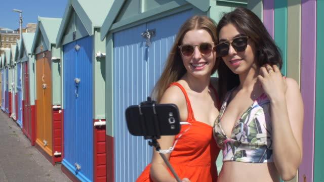 Two friends using a selfie stick