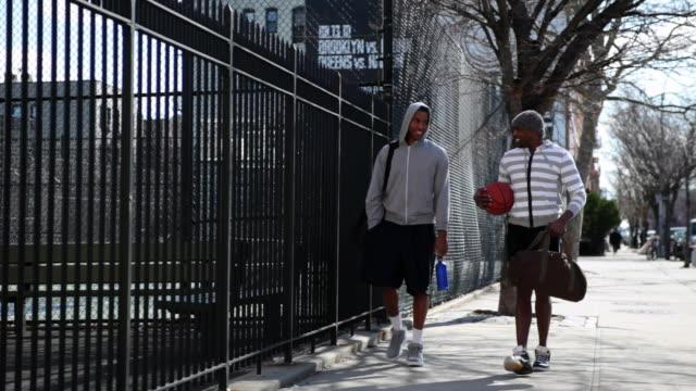 vídeos y material grabado en eventos de stock de ms tu two friends walking side of basketball court / brooklyn,new york,united states - capucha