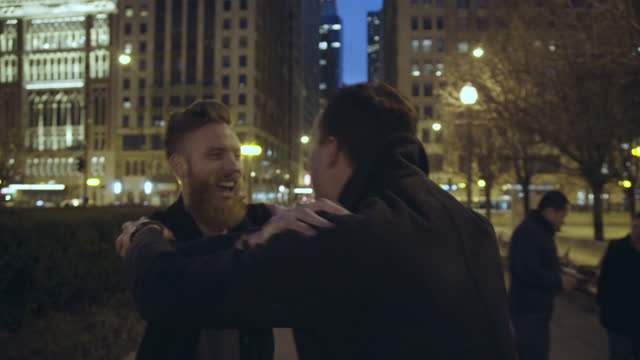 Two friends walking through Chicago at night grip each other by the shoulders and laugh.
