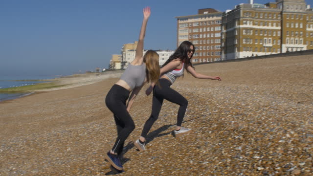 Two friends walking up pebbly beach. Brighton.
