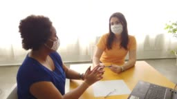 Two friends wearing protective face mask sitting in a office table.